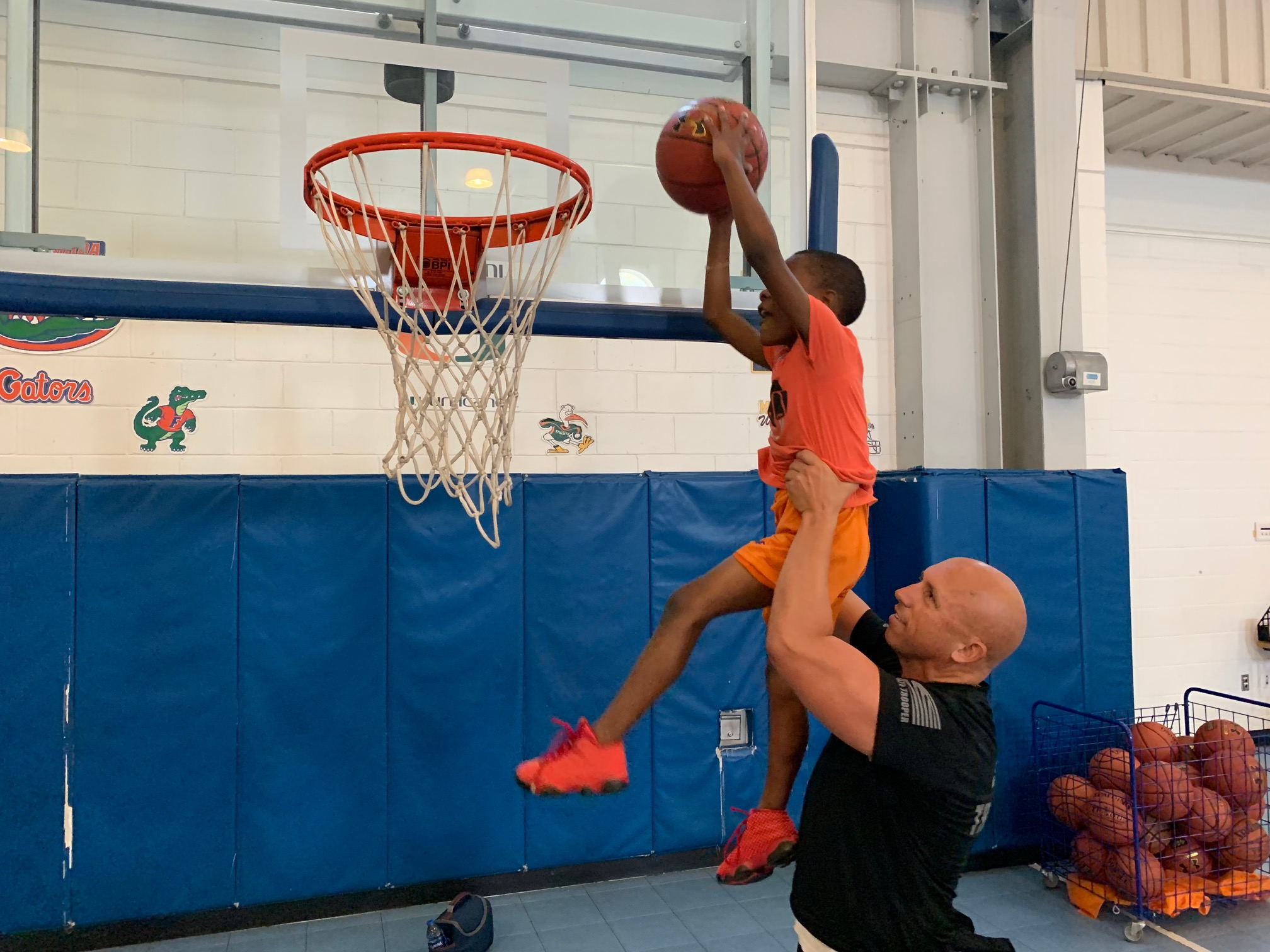 Lt. Greg Bueno helping a member of the Boys & Girls Clubs of Collier County dunk a basketball