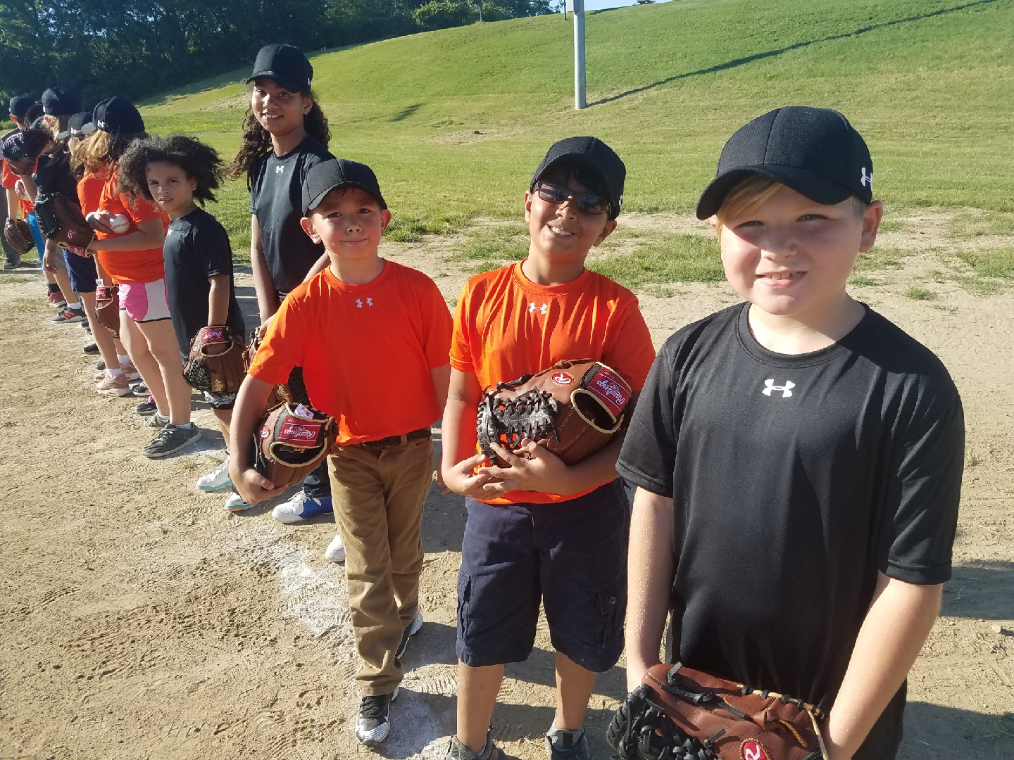 Youth posing with the equipment they received from participating in the Cal Ripken, Sr. Foundation Instructional Leagues