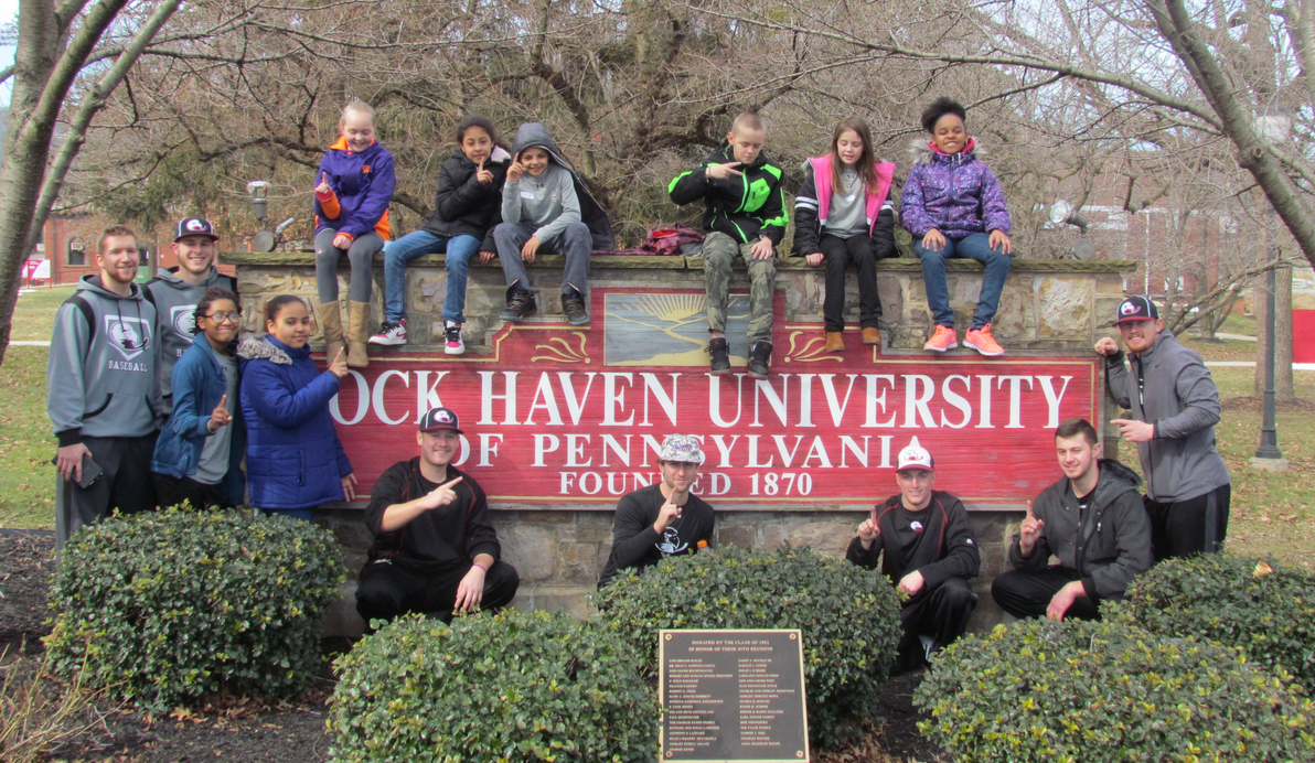 kids and mentors around lock haven university sign