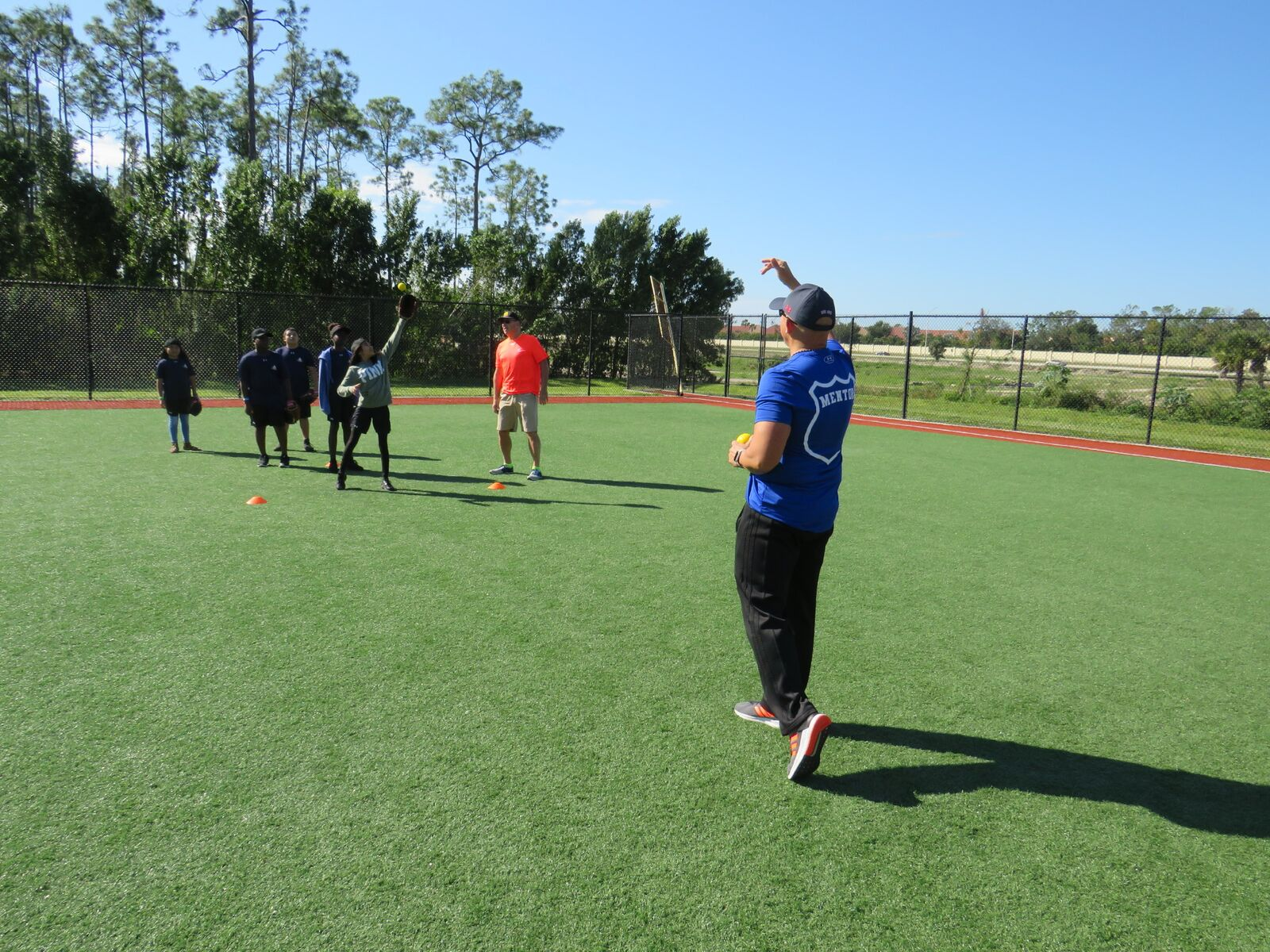 Lt. Greg Bueno working outfield drills with campers at the CRSF Naples Camp