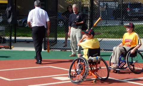 Baseball player in a wheelchair gearing up for a great hit at the plate.