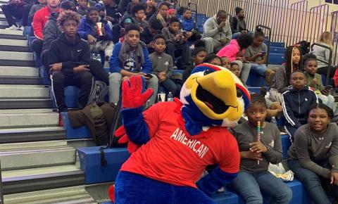kids sitting on bleachers with american university mascot