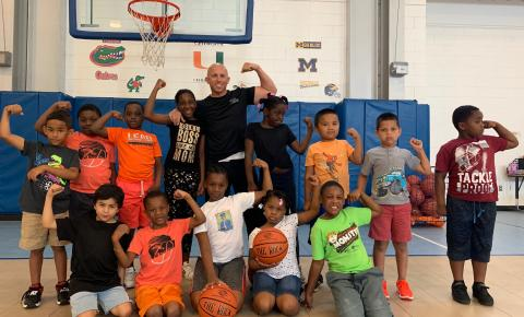 Lt. Greg Bueno posing with a group of youth from the Boys & Girls Clubs of Collier County