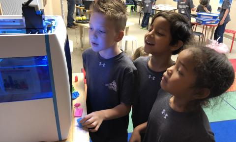 Three students observing a 3D printer in action